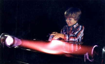 """Playing with a magnet and a plasma discharge tube, the """"Aurora Borealis Tube Display,"""" by Resonance Research Corporation."""